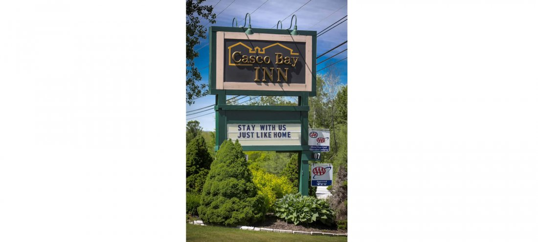 Green shrubs and trees around a green wooden sign that says Casco Bay Inn – Stay with us – Just like home