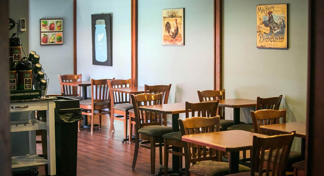 5.	Blue dining room with wood floors and several small dining tables for two and a coffee bar