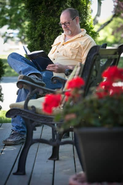 Man sitting on a patio reading with potted red flowers in the foreground