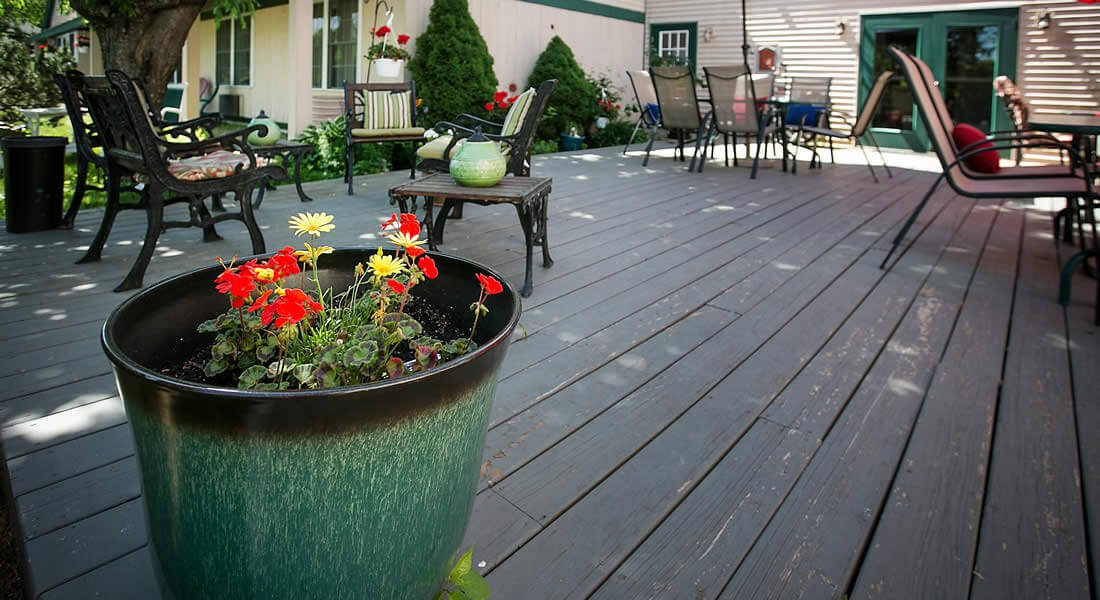 Wooden deck with tables and chairs and potted red and yellow flowers