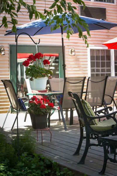 Wooden deck with patio umbrella tables and chairs and potted red flowers