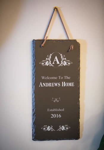 Brown sign hanging from a leather strap that says Welcome To The Andrews Home Established 2016
