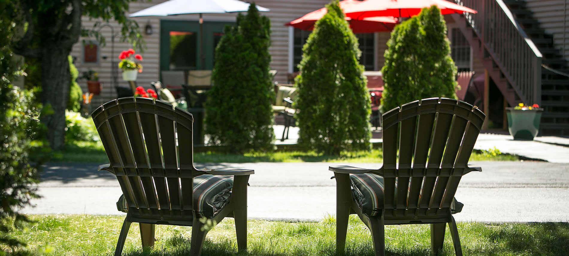 Two Adirondack chairs with green striped cushions sitting on grass