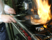 Close up view of a person's hands cooking on a stove with flames in an iron skillet