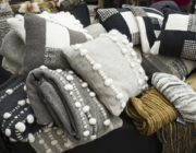 Pile of gray, black and white assorted pillows, blankets and yarn