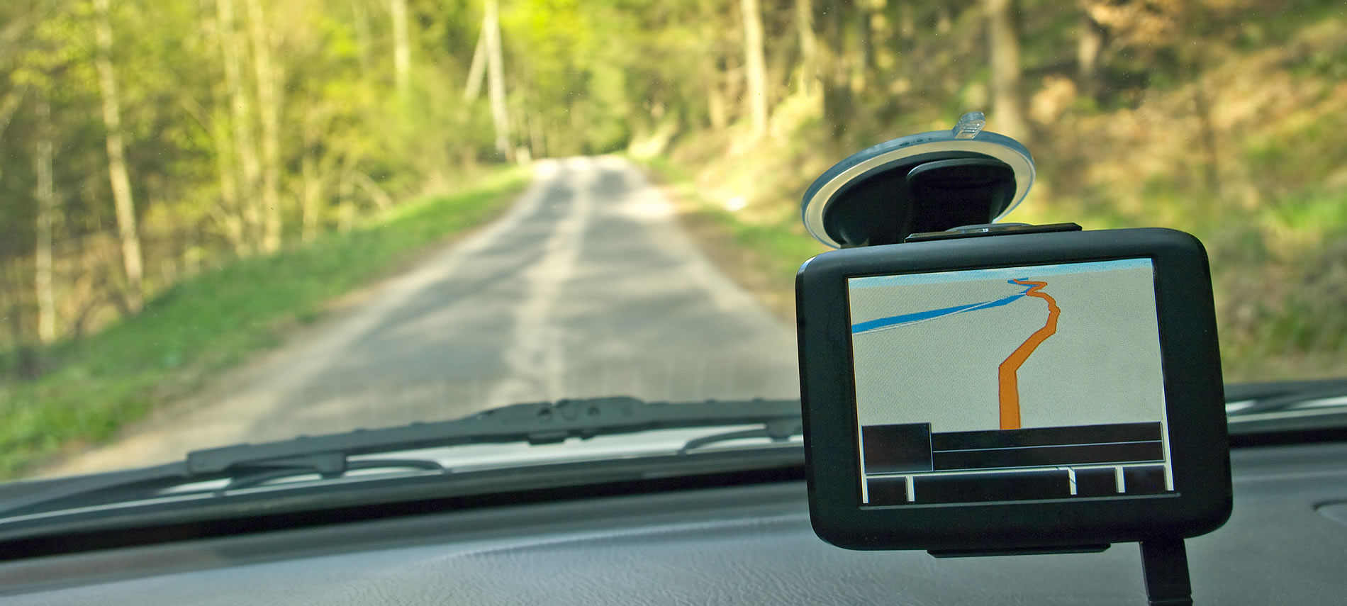 View through a windshield and GPS and a rolling road ahead surrounded by green trees
