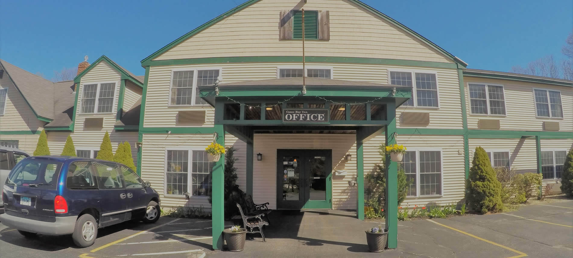 Two story tan building with green trim, gable room, green painted portico, double glass doors and an OFFICE sign