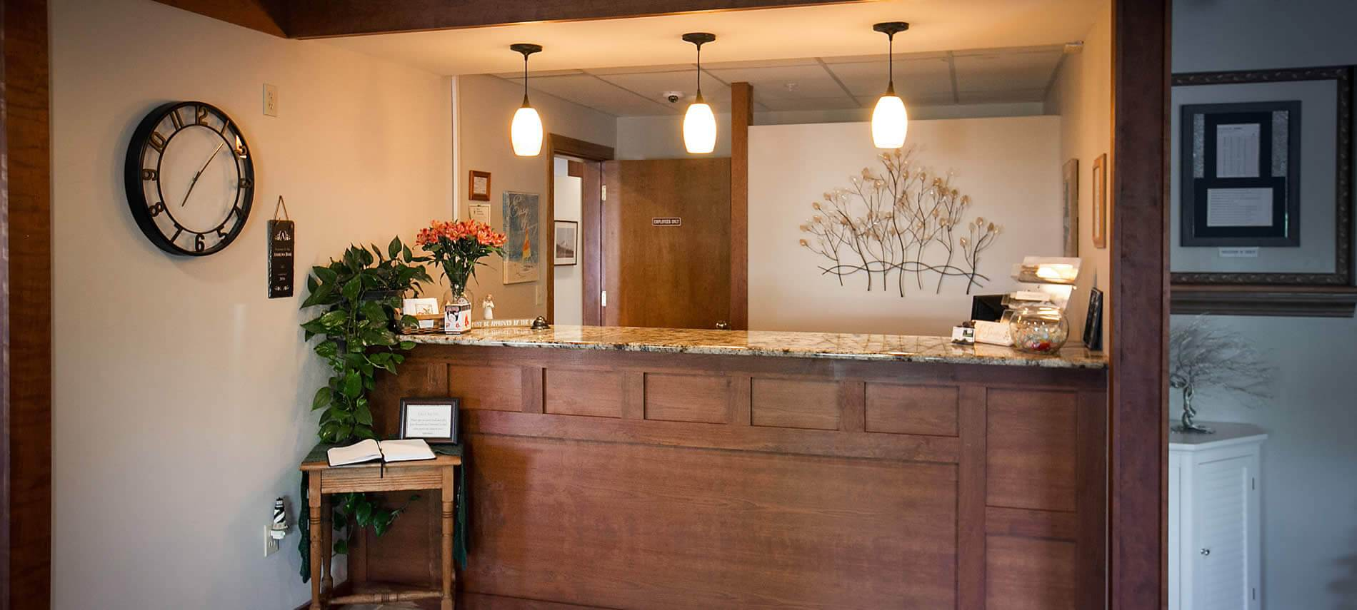 Wood stained welcome counter topped with fresh flowers and three hanging pendant lights
