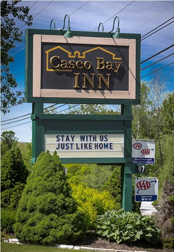 Picture of sign that says Casco Bay Inn with text below that says Stay with us just like home.