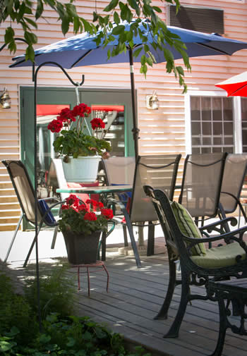 Wooden deck with several patio umbrella tables and chairs and potted red flowers